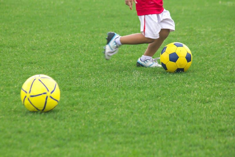 Ben av ungar sparkar fotboll royaltyfri bild