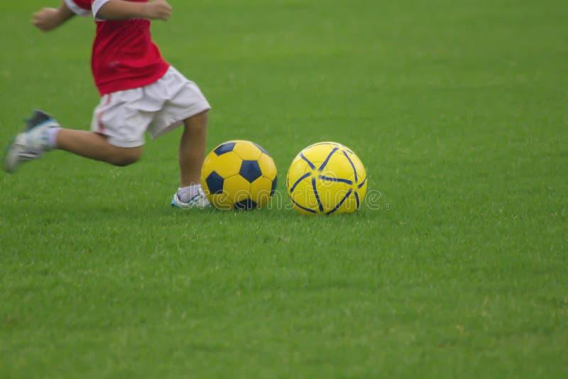 Ben av ungar sparkar fotboll arkivfoton