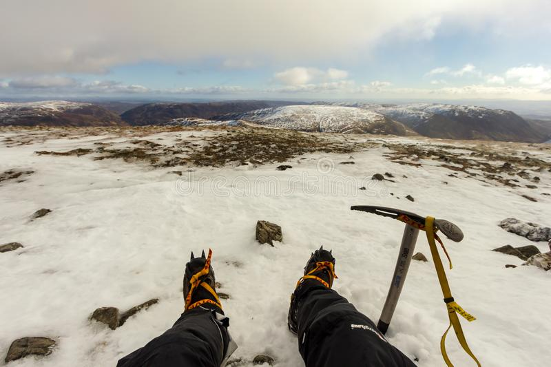 Ben Chonzie, Perth and Kinross/ United Kingdom - March 14, 2019: A view of a mountaineer with Grivel G12 new classic crampon. And ice axe in the snowy Scottish royalty free stock photo