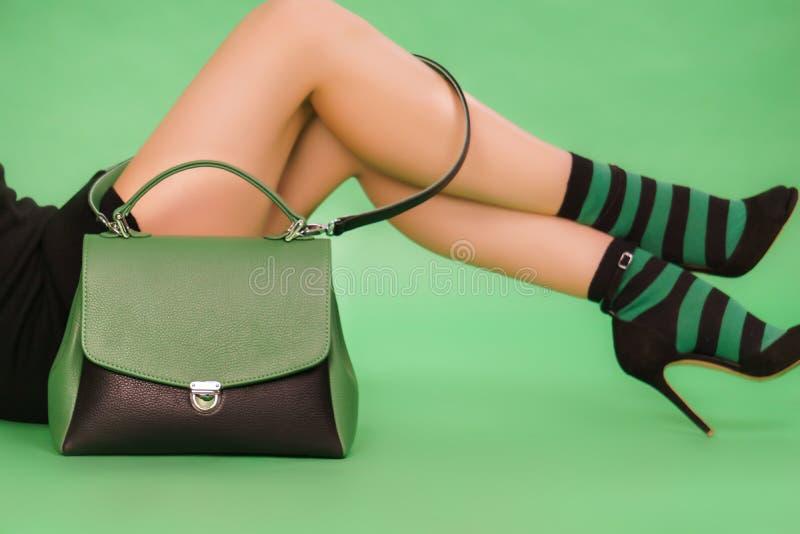 Ben för kvinna` s och gräsplan-svart handväska på en grön bakgrund arkivfoton