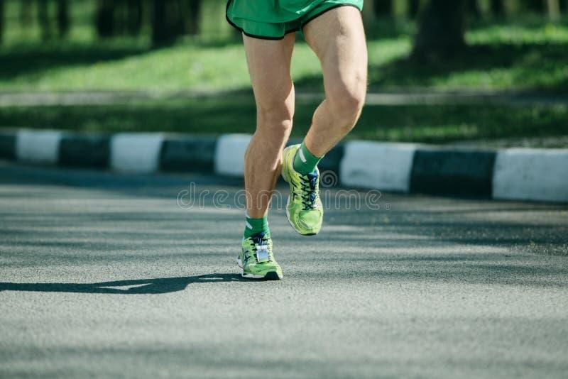 Ben för maratonlöpare och rinnande gymnastikskor av mannen som joggar som är utomhus- fotografering för bildbyråer
