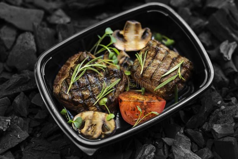 Ben fatto la bistecca di manzo con le verdure nel nero porta via la scatola fotografie stock