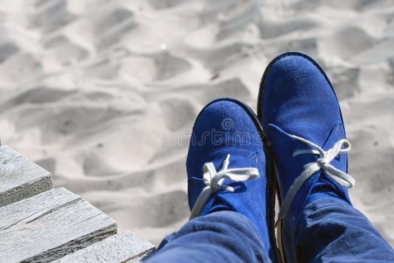 Ben i blåa mockaskinnskor på sanden royaltyfria bilder