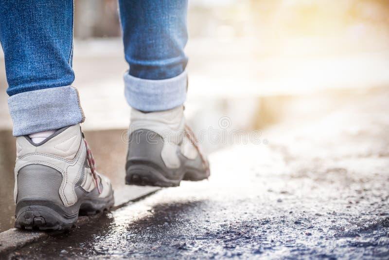 Ben i gymnastikskor går på en våt trottoarkant längs trottoaren Vår oss royaltyfri fotografi