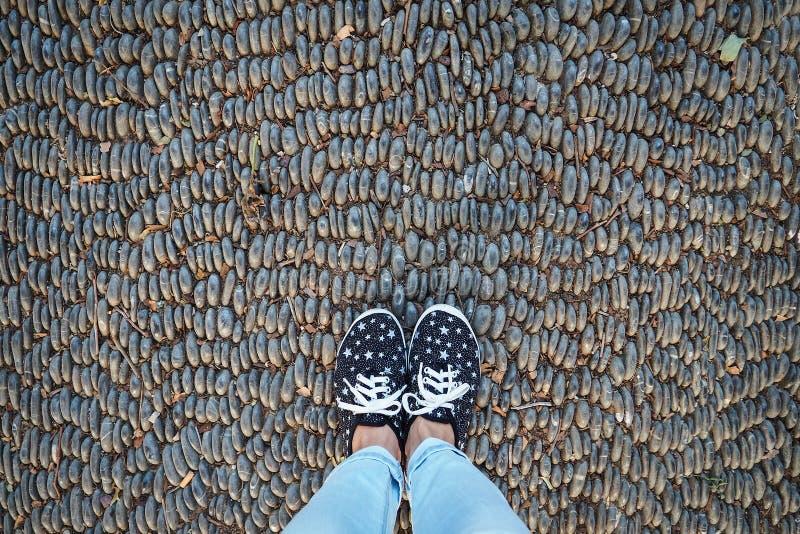 Ben i gymnastikskor och jeans, p? v?gen som stenl?ggas med stenar, b?sta sikt arkivfoto