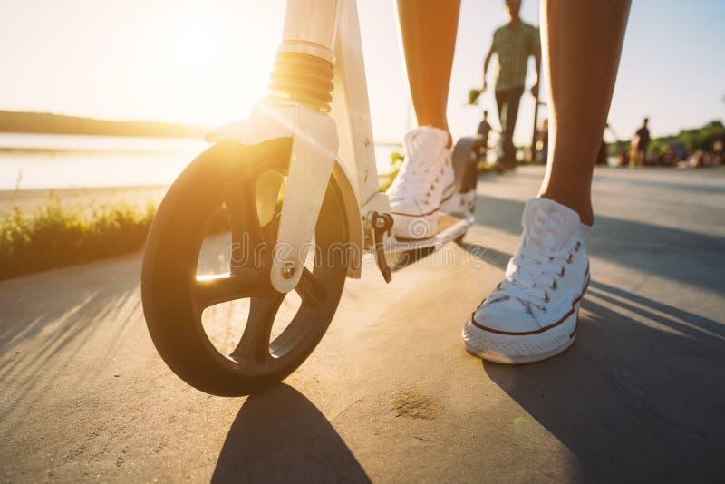 Ben i jeans och gymnastikskor på en sparksparkcykel ovanför sikt royaltyfri bild