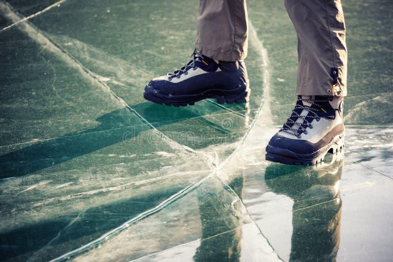 Ben i kängor på isen arkivbild