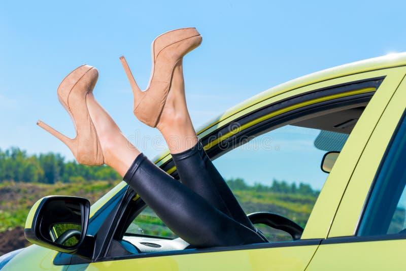 Ben i skor med höga häl som klibbar ut ur bilfönster arkivfoton