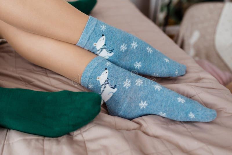 Ben med gulliga blåa sockor med vita björnar och gröna sockor på sängen kulöra sockor royaltyfria foton