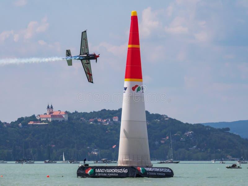 Ben Murphy z N540BM Zivko krawędzią 540 i latać nad Jeziornym Balaton przed Tihany przy Zamardi miastem dla Red Bull powietrza ra zdjęcia royalty free
