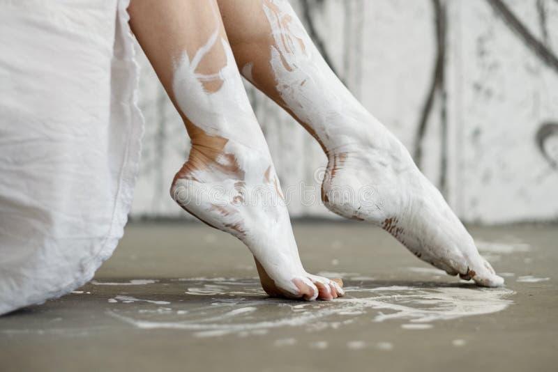 Ben och fot av en ung artistically abstrakt målad kvinna, ballerina med vit målarfärg royaltyfri foto