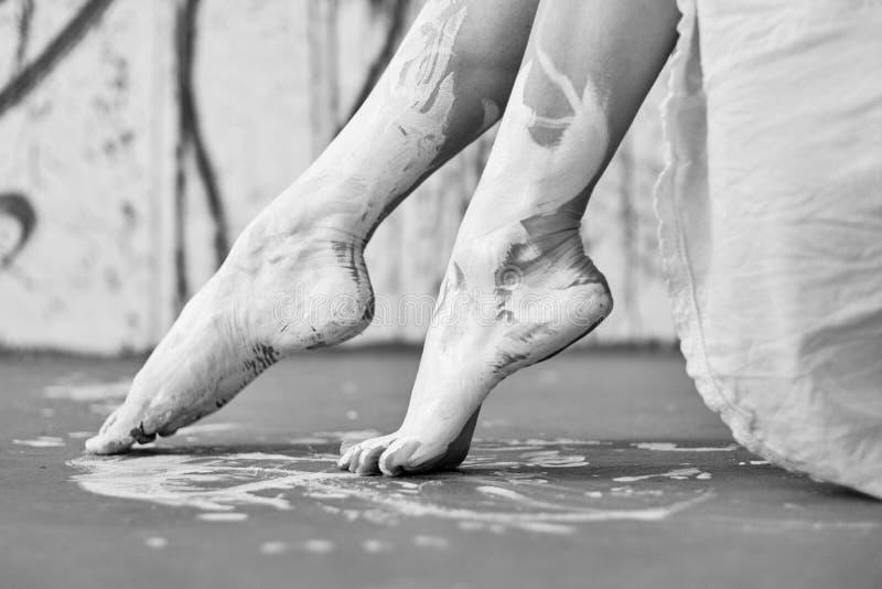 Ben och fot av en ung artistically abstrakt m?lad kvinnaballerina med vit m?larf?rg Id?rik kroppkonst arkivbild