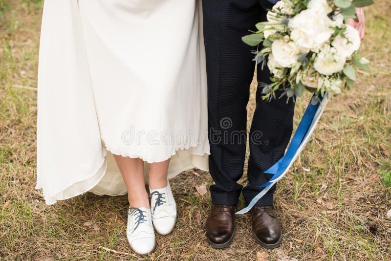 Ben och fot av gifta paret i stilfulla skor arkivfoton