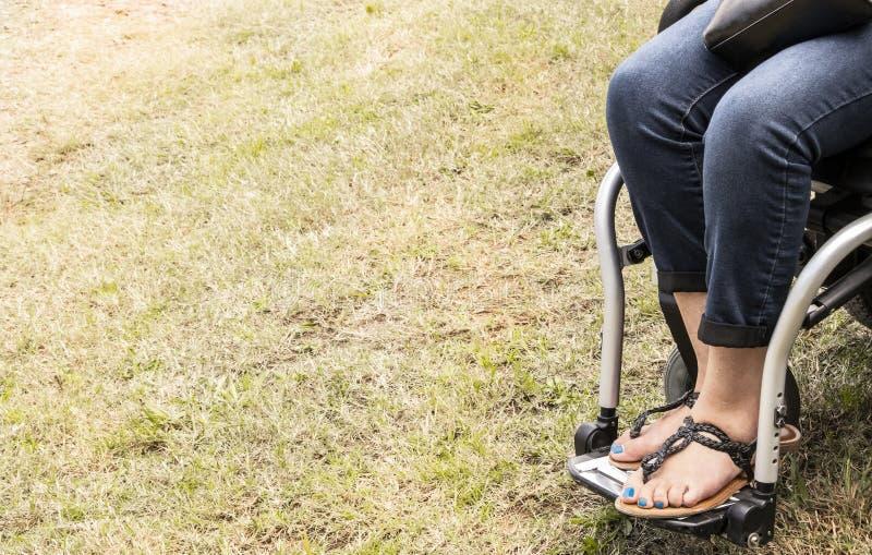 Ben och fot av kvinnan i rullstol med blå målad tånaglar och sandaler och blå jeans och en svartläderhandväska som kantjusteras p arkivfoto