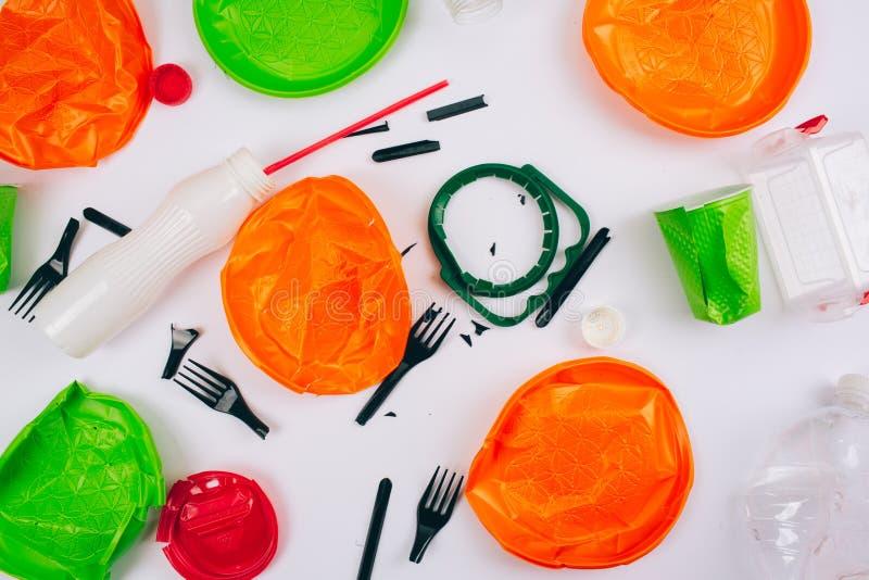 Ben plastic vrij Sparen ecologie Gebroken kleurrijke platen voor éénmalig gebruik, vorken, koppen, fles, stro, deksels op witte a royalty-vrije stock fotografie