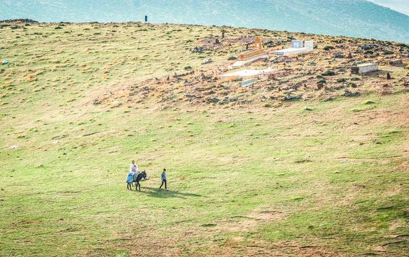 Ben Smim Maroko, Październik, - 04, 2013 Berber rodzina z osła omijaniem małym cmentarzem na łące obrazy stock