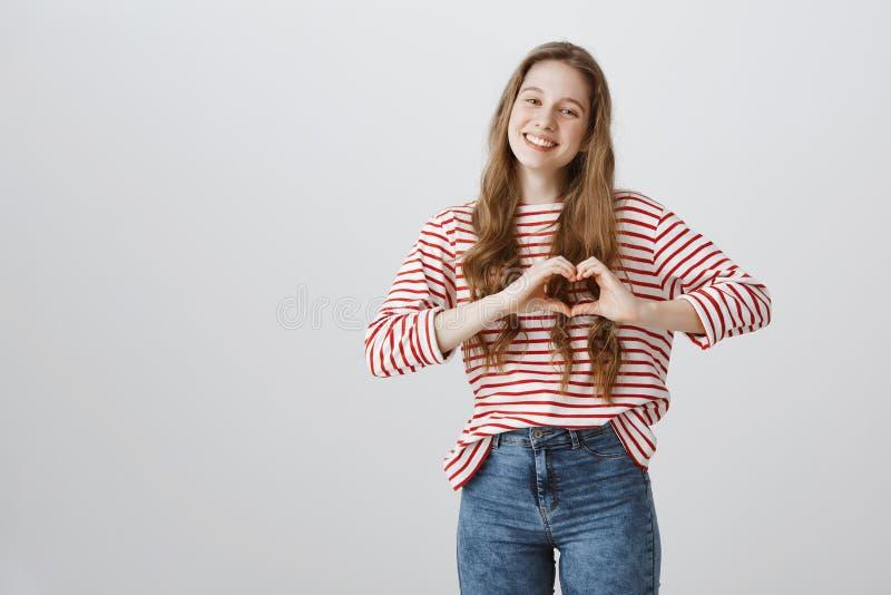 Ben voor altijd Mijn Portret van hartstochtelijk aantrekkelijk hartgebaar over borst tonen en blondemeisje die ruim glimlachen stock foto's