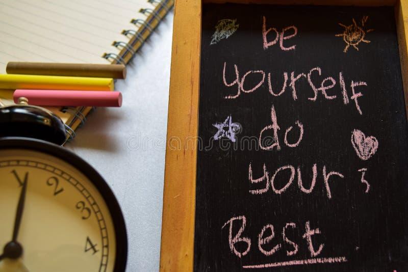 Ben zelf doen uw beste op uitdrukkings kleurrijke met de hand geschreven op bord, wekker met motivatie en onderwijsconcepten stock afbeelding