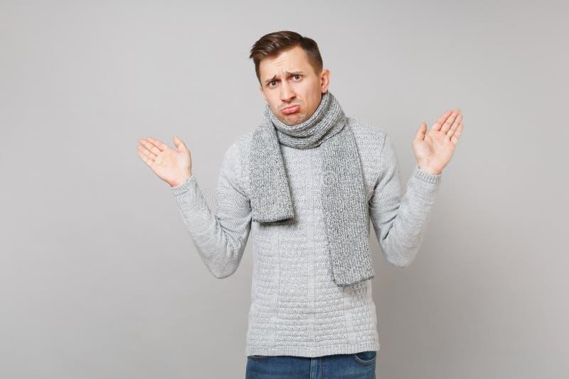 Benachteiligter junger Mann in der grauen Strickjacke, schmollende Lippen des Schals, ausgebreitete Hände lokalisiert auf grauem  stockfotos