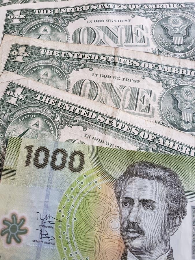 benadering van Chileens bankbiljet van 1000 peso's en Amerikaanse dollarrekeningen royalty-vrije stock afbeeldingen
