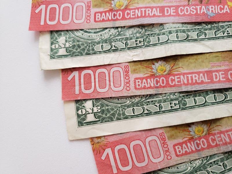 benadering van Costa Rican-bankbiljetten en Amerikaanse dollarrekeningen op witte achtergrond stock afbeeldingen