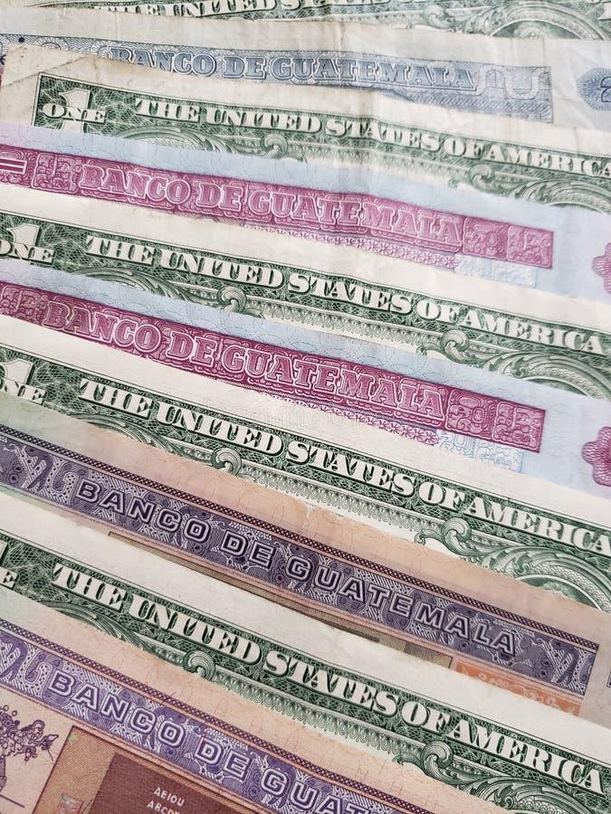 benadering van Guatemalaanse bankbiljetten en Amerikaanse dollarrekeningen stock afbeelding