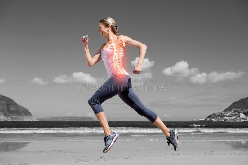 Benadrukte ruggegraat van joggingvrouw op strand stock foto's