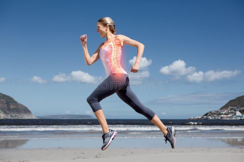 Benadrukte ruggegraat van joggingvrouw op strand stock foto
