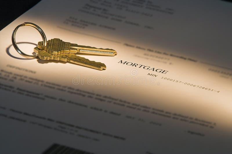 Benadrukte van het hypotheekdocument en huis sleutels stock fotografie