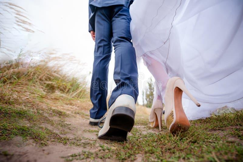 Benbrudar och brudgummen, nygifta personer går royaltyfri bild