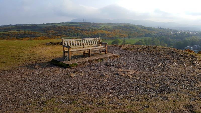 Bench на верхней части холма с облаками на заднем плане стоковая фотография rf