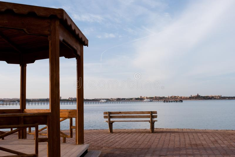 Bench and alcove on break beach. Big wooden alcove and empty bench. Empty place for meeting near ocean. Bench and alcove on break beach. Big wooden alcove and royalty free stock photography