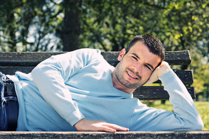 Bench attitude. Relaxed handsome man on a bench in a park stock photo