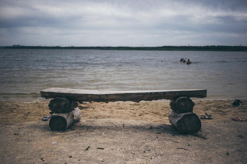 Bench on the beach. Rest on the shore of a pond stock photography