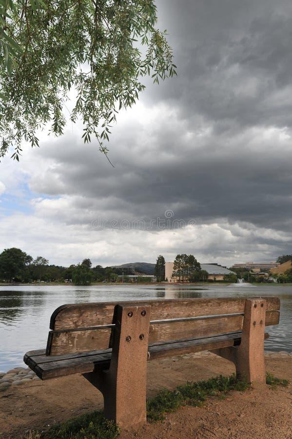 Download Bench Da Un Lago E Da Un Albero Con Le Nuvole Minacciose. Fotografia Stock - Immagine di legno, nubi: 30827654