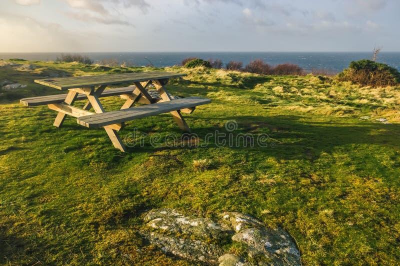 Bench em uma costa rochosa durante um por do sol imagens de stock