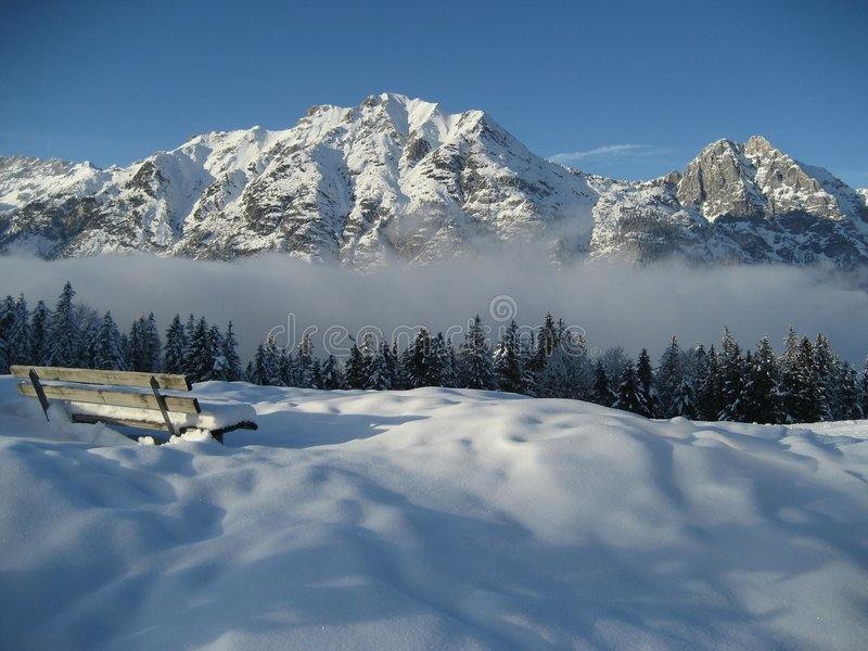 Bench en la nieve con las nubes y la montaña fotografía de archivo