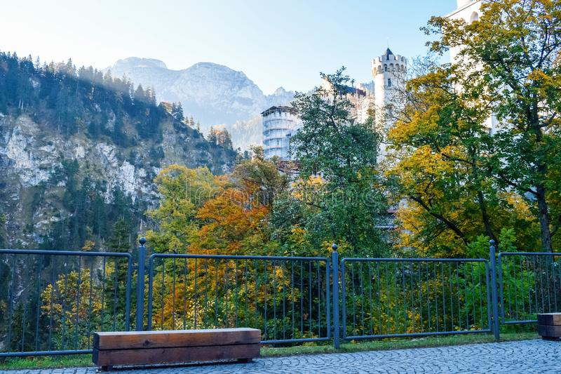 Bench en metalen hek met het kasteel van Neuschwanstein op een achtergrond in de bergen in Alpen royalty-vrije stock afbeelding