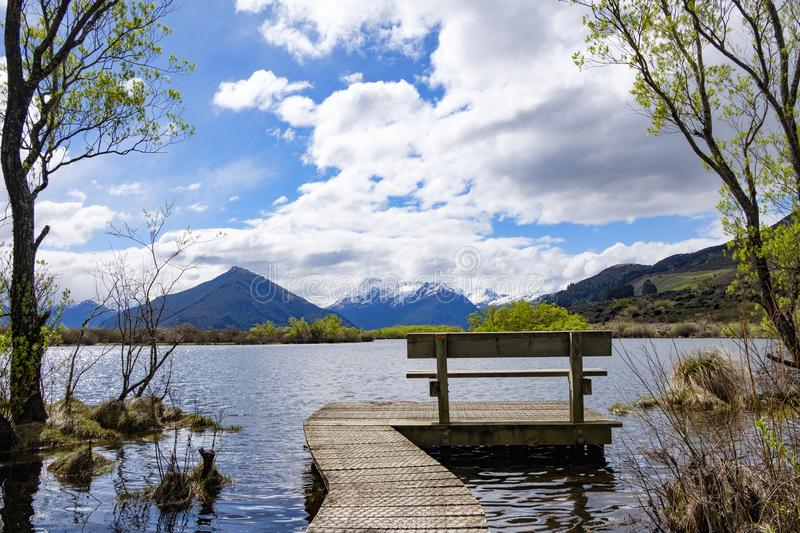 Bench at the end of a boardwalk by a lake in South Island, New Zealand stock image