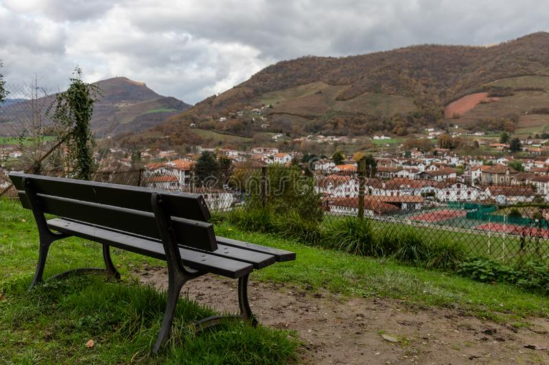 Bench in a france place with the village in front. Mountains & clouds stock photos