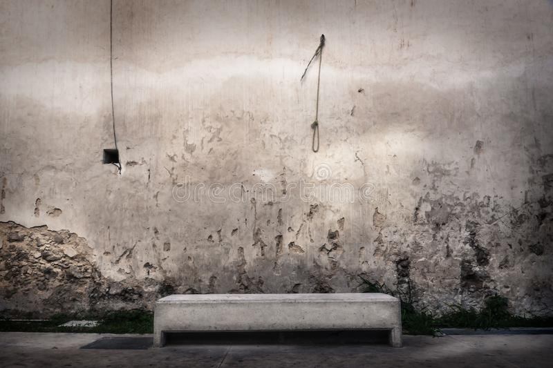 Bench in front of abandoned wall with hangman knot hanging at the wall, Merida, Mexico. Concrete bench in front of abandoned wall with hangman knot hanging at stock photos