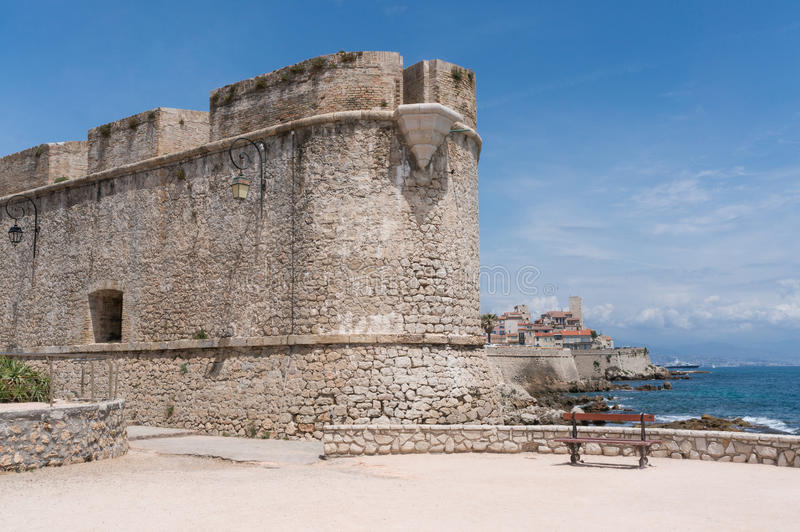 Bench in front of Antibes& x27; historical city walls. A bench in front of the historical city walls of Antibes that were built in the 10th century to protect stock images