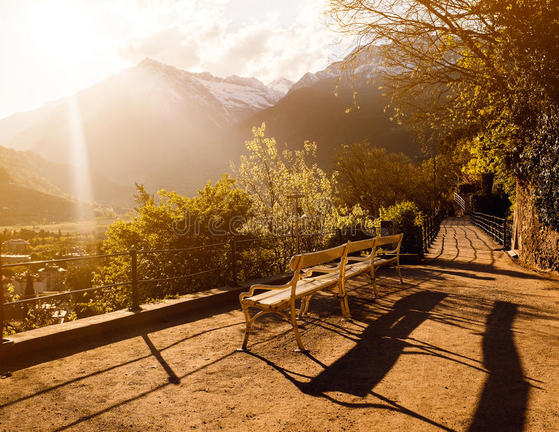 A bench in front of the hills during sunset. A bench with no people and a shadow standing in front of the sun and beautiful mountains with peaks seen nearby a royalty free stock images