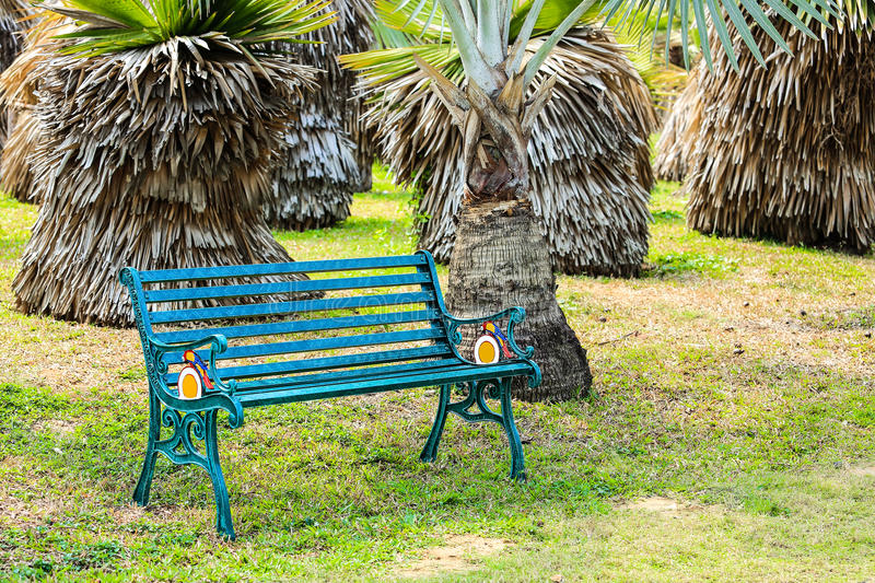 Bench in garden. Steel bench in palm garden stock image