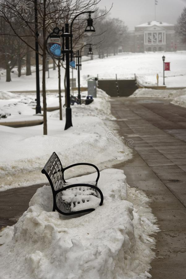 Bench hidden in snow at plaza in Madison Wisconsin stock photography