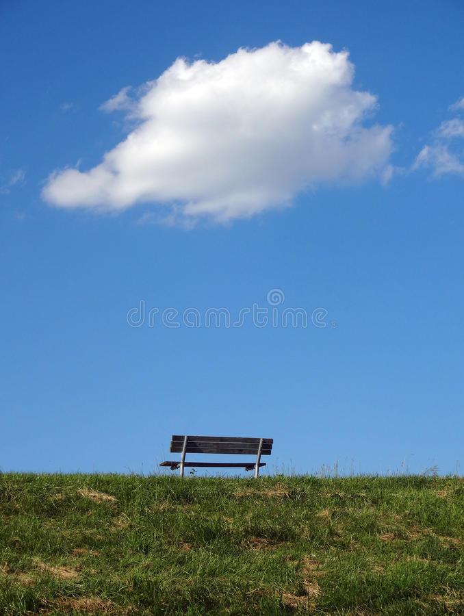 Bench on a Hill with Single White Cloud Above It. A lone wooden bench sits atop a grassy hill with a single white cloud thought bubble above it stock photos