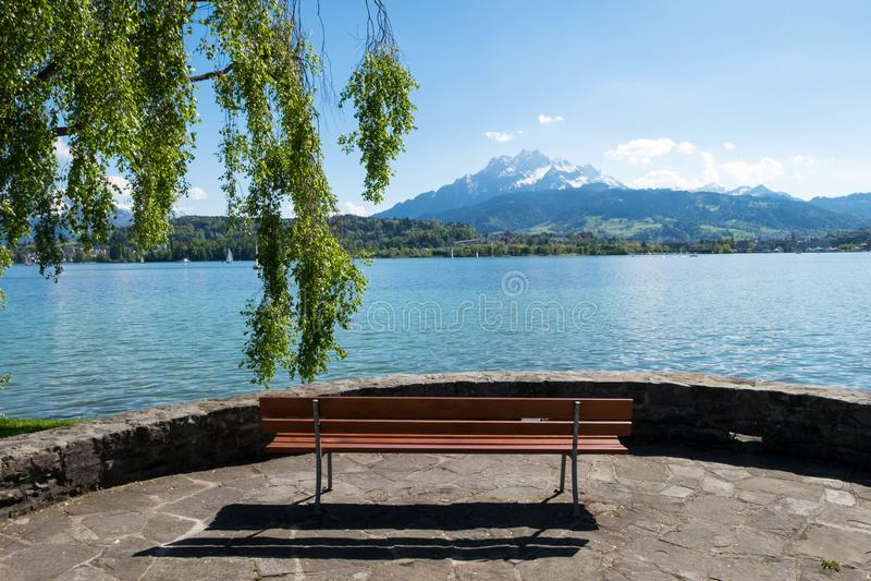 Bench i fronti alla vista del lago geneva e del paesaggio delle alpi immagine stock libera da diritti
