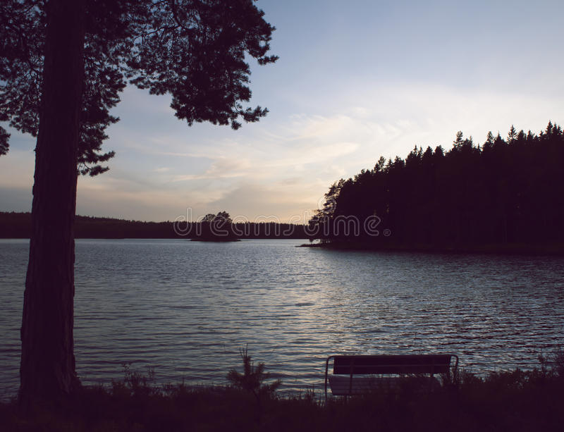 Bench by lake in beautiful sunset. An empty bench facing a lake by a beautiful, colorful, summer sunset. Värmland, Sweden royalty free stock photos