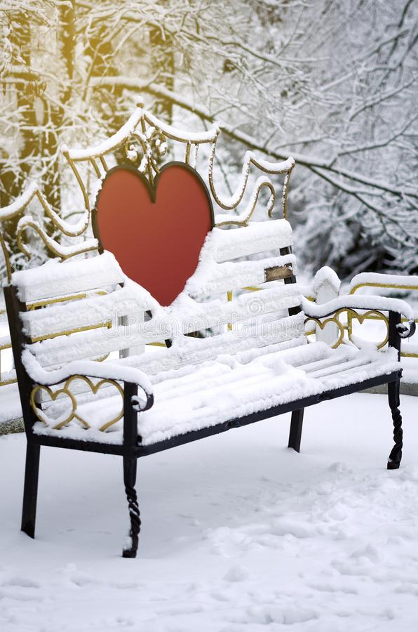 A bench for lovers in a winter park. Vertical orientation stock image