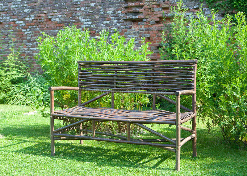 Bench reed sun. Garden bench made of reed standing in the green in the sun in front of a brick wall stock photos